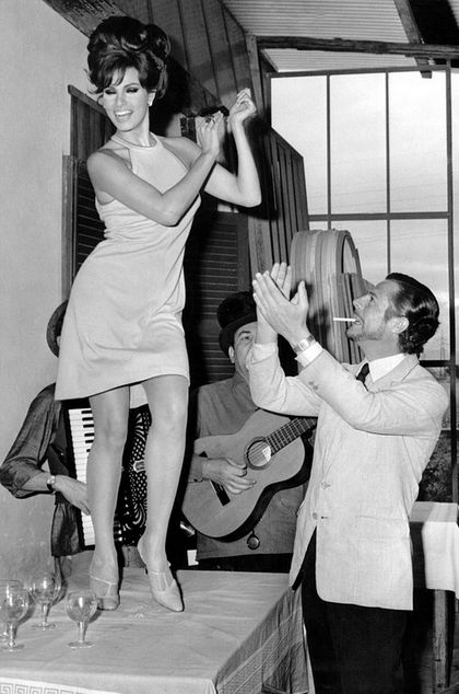 8 Raquel Welch dancing on a table while Marcello Mastroianni claps 1966.jpg