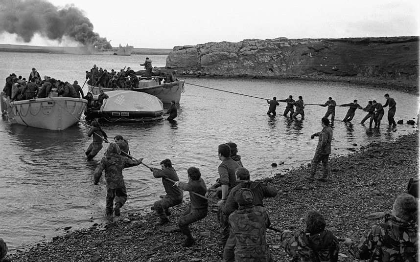 5 Survivors from HMS Sir Galahad (ablaze in the background) are hauled ashore by colleagues at Bluff Cove East Falkland after the ship was hit by an Argentinian air attack on June 29 1982 during the Falklands conflict.jpg