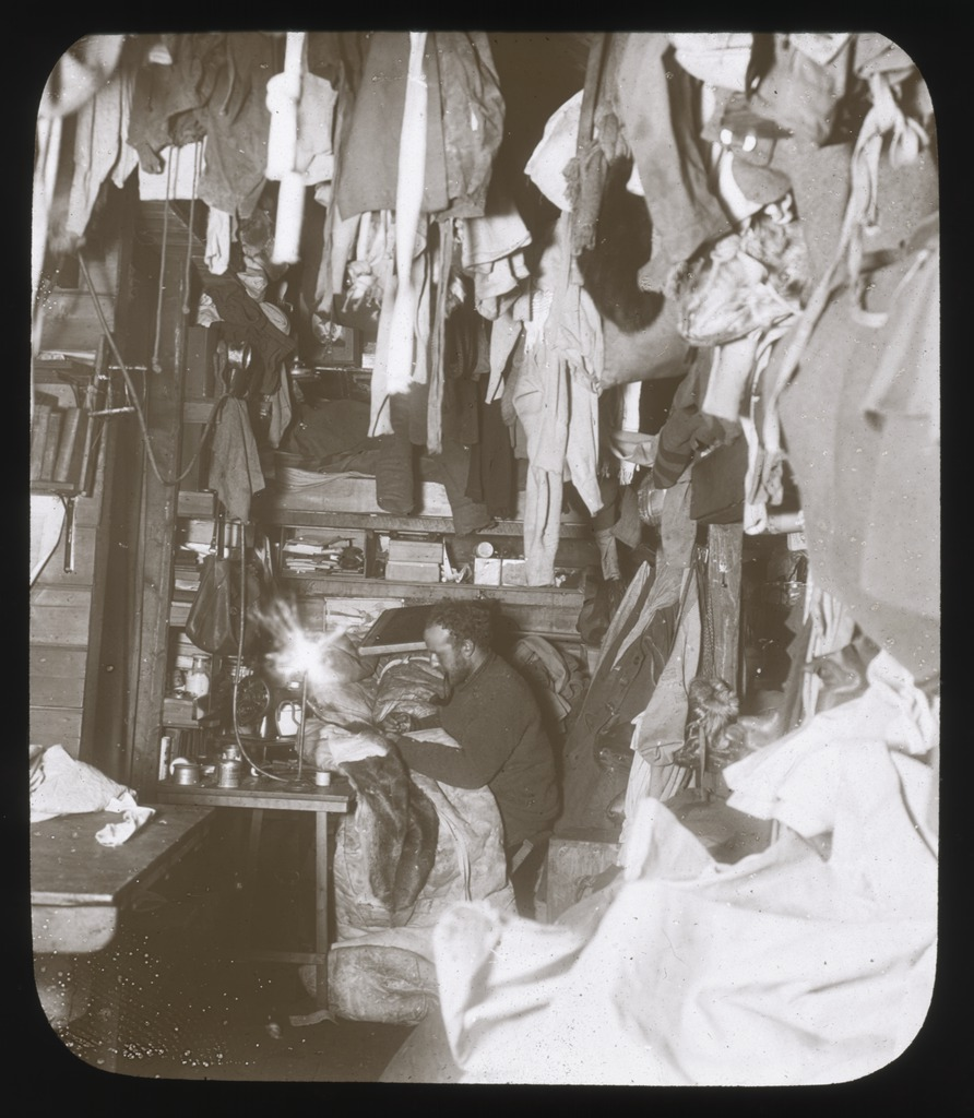 a-corner-of-the-hut-bage-mending-his-sleeping-bag-australasian-antarctic-expedition-1911-1914-1_6173954058_o.jpg