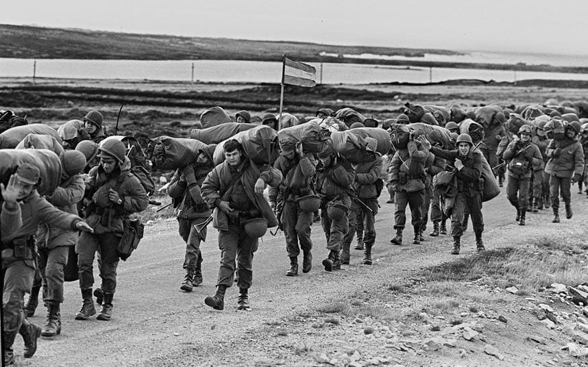 7 Argentine soldiers march on their way to occupy the captured Royal Marines base in Puerto ArgentinoPort Stanley.jpg